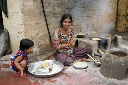 Lakshman Singh's niece making chapatis, with the granddaughter assisting